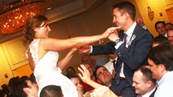 Guests lift bride and groom on chairs as Retrospect Band plays a lively hora