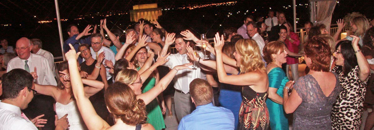 Wedding guests dance as Retrospect performs at a rooftop venue overlooking the Lincoln Memorial