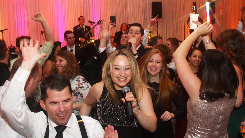 Retrospect Band's vocalists Tara and Mike making their way onto a crowded dance floor at a recent country club wedding in Rockville MD