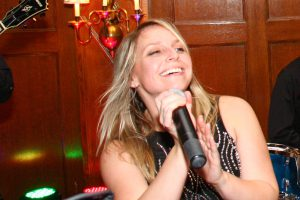 Retrospect Band vocalist Aimee smiles while singing at a wedding in DC