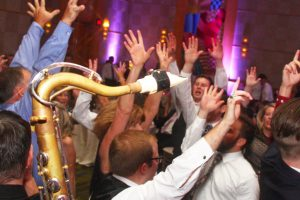 Close up as a tenor saxophone makes its way through the crowded dance floor at a recent Retrospect Band wedding in Bethesda