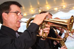 Retrospect Band leader Larry leads horn section on flugelhorn at a recent Eastern Shore wedding by the water