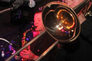 Close up shot of Retrospect Band's horn section at a club showcase