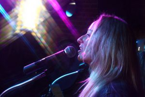 Colorful shot of vocalist Tara performing at a recent Retrospect Band showcase in Bethesda